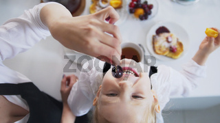 Top view of mom and her little girl drinks tea and eats cherry