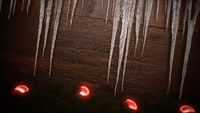 Closeup red balls and icicles on wood background