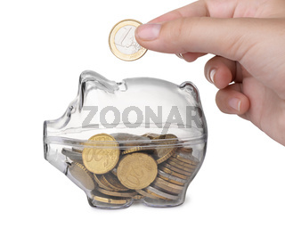Close up of hand putting coin into piggy bank