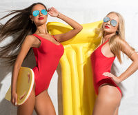 Two sexy girls with yellow air mattress near sunny wall