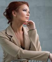 Woman in fashionable beige pantsuit in studio
