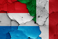 flags of Luxembourg and Italy painted on cracked wall