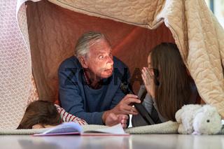 Opa und Enkel mit Taschenlampe machen Unfug