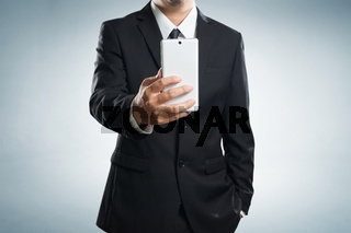 Smart businessman in black suit standing while make a selfie by hand phone on grey background .