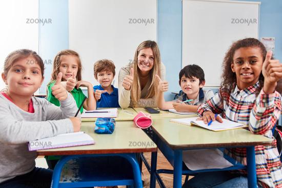 Glückliche Schüler halten die Daumen hoch
