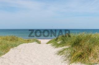 Deutsche Ostseeküste  mit Sanddünen, Gras, Wasser und blauem Himmel