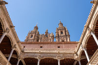 Casa de la Conchas and its carved balconies with Clericia church in Salamanca Spain