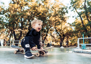 Young kid sitting in the park on a skateboard.