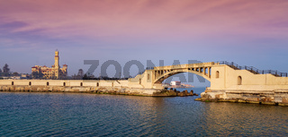 Bridge in the sea at Montazah park with the Royal palace in the far distance with calm sea at sunrise time, Alexandria, Egypt