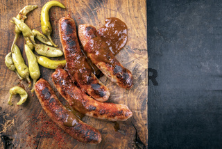 Traditional barbecue German Bratwurst with hot sauce and peperoni as top view on an old cutting board with copy space right