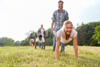 Junge Leute spiele Schubkarre zusammen
