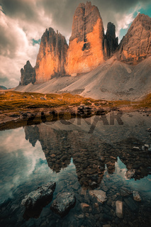 Three Peaks in the Dolomites reflecting in a lake, Italy