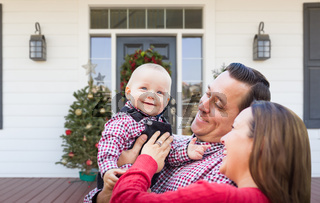 Happy Young Family On Front Porch of House With Christmas Decorations