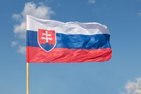 Slovak national flag waving on wind at blue sky background