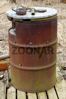 Large rusty barrel is used in the forest as a public ashtray.