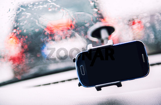 Smart phone on holder, rainy weather seen through wind shield, cellphone with black mock up blank on screen. Advertisement for traffic and navigation GPS apps concept close up image, no people