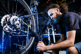 Young stylish bearded, with long hair Caucasian male mechanic worker at a bicycle workshop uses a tool for repairing Cranksets