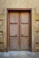 Grunge wooden aged door on grunge stone bricks wall