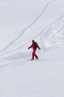 Snowboarder downhill on snowy off-piste slope after snowfall