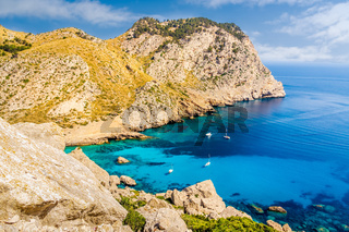 Coastline with cliffs, turquoise water and yachts. Cala Figuera beach on Formentor peninsula, Mallorca