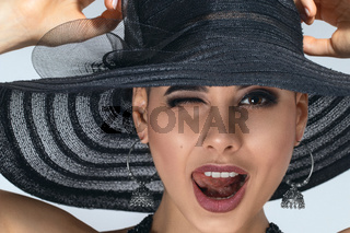 Studio portrait of beautiful happy young woman in sun hat