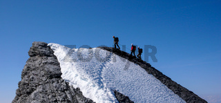 mountain guide leading two male clients to a rocky ridge and onwards to a high alpine summit