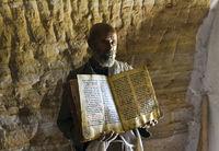 Orthodoxer Priester der Felsenkirche Mikael Mellehayzengi zeigt liturgisches Buch,Tigray,Aethopien