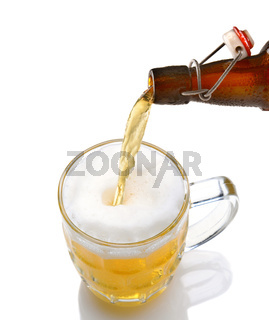 Cold beer pouring from a bottle into a mug on a white background with reflection.