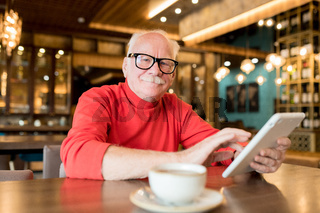 Content elderly man connecting to wifi in cafe