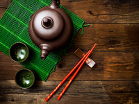 Teapot on green bamboo mat. Top view