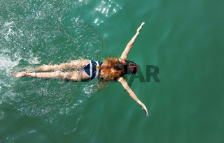 Aerial top down view of a girl wearing swimming mask in the sea