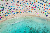 Aerial view of sandy beach with umbrellas and sea