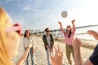friends playing volleyball on beach in summer