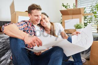 Verliebtes Paar bei der Planung von Hausbau