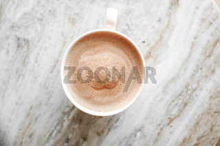 Morning coffee cup with milk on marble stone flat lay, hot drink on table flatlay, top view food photography and recipe inspiration for cooking blog or cookbook