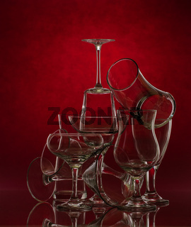 Composition of glass glasses of different shapes on a red background. Art photography.