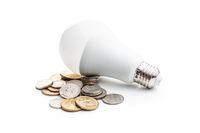 Energy saving light bulb. LED light bulb and dollar coins.
