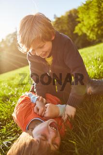Junge kitzelt lachende Freundin beim Spielen