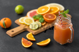 mason jar glass of fruit juice on slate table top