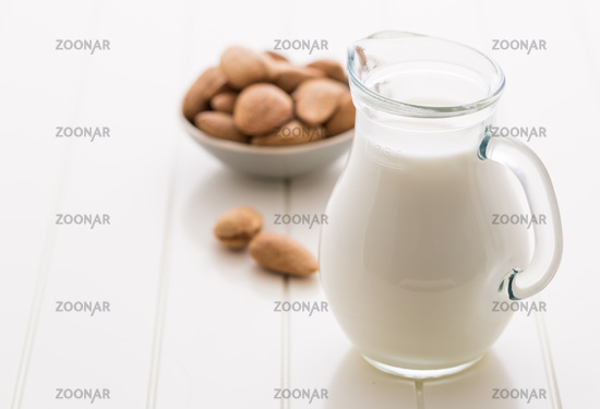 Jar of almond milk with almond nuts on white background