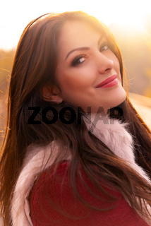 Close-up portrait of a gorgeous romantic young woman with beautiful long brown hair, in nice warm autumn sunlight, looking at the camera and smiling. Shot in natural light, retouched, vibrant colors