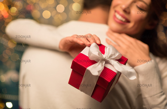 close up of couple with christmas gift hugging