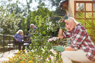 Erschöpfte Seniorin mit Blumen auf Terrasse