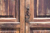 metal knocking knob on wooden door closeup -