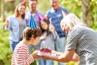 Geburtstagskind pustet Kerzen aus auf der Torte