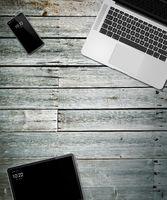 Laptop, tablet and phone set mockup on a wooden background. 3D render