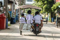 Children are coming back from school. Group of children riding a motorcycle - tricycle, Thailand.