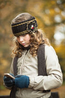 Teenager girl texting with cellphone in an autumn day