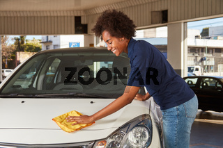 Mechaniker Azubi mit Lappen beim Polieren von Auto