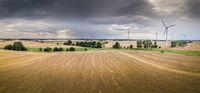 Luftaufnahme einer Landschaft bei aufziehendem Gewitter mit Windrädern